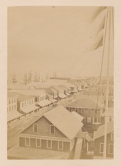 Photographic print of British Guiana, with houses in the foreground and ships in the background