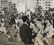 Photograph captioned: Rioting in Port Said brought under control, with crowds and soldiers visible in a scene of tension