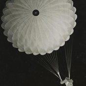 Photograph of descending parachutist from beneath; likely taken at night