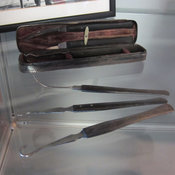 Photograph of pocket instrument with three individual instruments displayed in front of the case