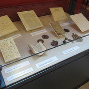 Photograph of exhibition case 4 showing Waterloo spoils, books and manuscripts.