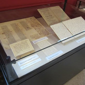 Photograph of exhibition case 6 showing fragmentary proof, playbill and manuscripts.