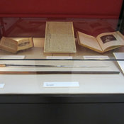 Photograph of exhibition case 7 showing swordstick, portrait, manuscript and books.