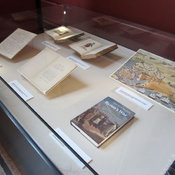 Photograph of exhibition case 9 showing letter, pamphlet, books and facsimile print.