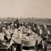 Photograph of officers at a dining table laid out in the open air with attendants standing on the side