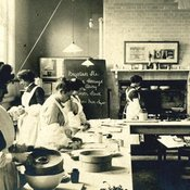 Group of about six women students at work in a kitchen with a chimney in the background