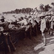 Photographs showing a row of soldiers aiming rifles standing behind a defensive earthwork wearing uniform with shorts and pith helmets