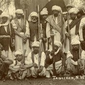 A group photo of Afghan tribesmen with guns in turbans along with one man in a pith helmet