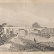 Scenic view of a river and bridge with a train crossing. A man and child fish with nets in the foreground.