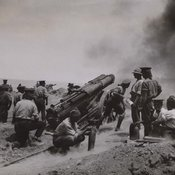 group of soldiers around a large gun on a carriage with a cloud of black smoke on the upper right after firing