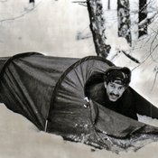 Picture of smiling BRIXMIS officer in a one man tent, in a snow covered forest