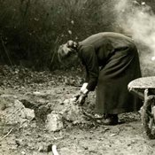 Photograph of woman bent over a shovel with a smlking cooer in backtround and wheelbarrow in foreground