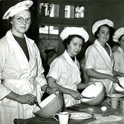 Photograph of six cookery students in white coats and hats all holding mixing bowls