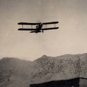 Photograph of bi-plane flying over arid hills