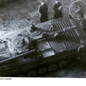 Aerial picture of a Soviet pictured next to a military tank aiming his rifle directly at the camera