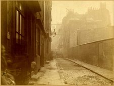 image of a narrow London street with a row, probably of dwellings on left and a brick wall to the right and buildings in the distance behind, grey and misty atmosphere