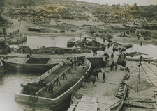 Photograph showing a view of 'V' beach at Gallipoli, taken from the deck of the SS River Clyde. The encampment and support ship, as well as soldiers are visible