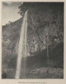 Photograph showing a tall waterfall concealing the mouth of a cave
