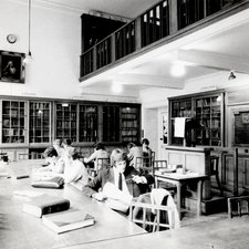 photograph of a large reading room with bookshelves enclosed behind glass doors, two tables with several readers, in the foreground a male student in coat and tie reads a newspaper; above on the wall a portrait of Alexander Pope
