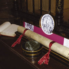 Photograph of King's College charter rolled and tied with scarlet ribbons in its document case to protect it from damage, there is a circular projection to the cases; to protect the seal and above that, inside the lid, is an engraved image of King George the fourth