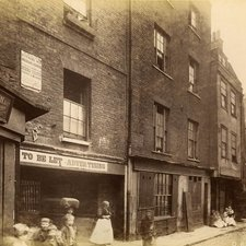 Photograph of a Victorian era street with groups of women and children standing or sitting before worn brick and timber buildings