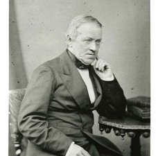Image of Sir Charles Wheatstone in small wire-framed glasses seated with his left elbow resting on a small wooden table