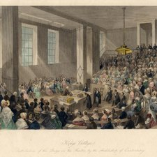A colour engraving of academic prize giving with a scholar in a gown bowing across a table to the Archbishop of Canterbury presenting a folder to him. This happens at the centre of a tiered lecture theatre filled with spectators, many of whom are ladies in lace bonnets