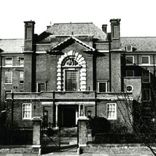 photograph of large brick school with extensive porch on front and large arched window above