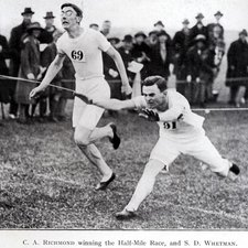 published photograph of two men crossing a finishing line, the winner, identified as C A Richmond stretching forward with spectators in the background
