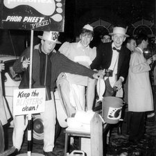 Image of a group of unconventionally dressed students, two wearing straw boater hats, one young man dressed as a female nurse bathing his feet and smiling broadly, next to him a student assisting near a sign saying, Phisohex phor pheet phree!