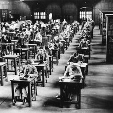 Large panelled hall containing rows of desks at which students sit studying, some desks unoccupied