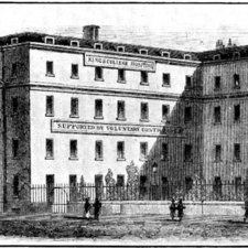 Engraving of four storey L-shaped hospital building with garden behind iron railings, pedestrians in foreground