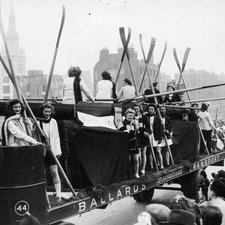 Photo of a lorry with the King's women's rowing team on back some in a scull, several holding oars in a parade with a crowd in the foreground and being followed by a marching band