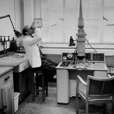 Randall, a balding man in a white coat, with his head leaned back peering upwards into an object. He sits on a stool in a laboratory with an electron microscope to his right