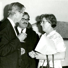 three people conversing with Maurice Wilkins on left, and unknown man behind and Jean Hanson on right