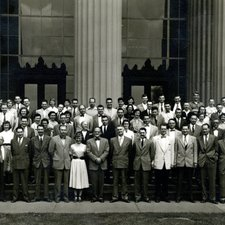 group photo of large number of people on steps of a large building with classical columns