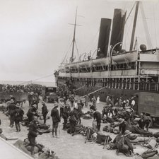 large number of people including troops on quay with large ship in background
