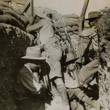 photograph of four men in a trench, two facing right, one operating a high level gun, one apparently with a periscope; two seated below facing right