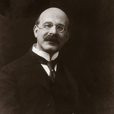 image of Gollancz seated in suit, balding gentleman with large moustache, smiling, wearing pince-nez glasses attached to a cord
