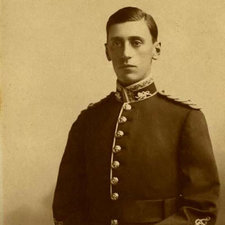 Photo of Second Lieutenant Brocklebank wearing a uniform with braiding and brass buttons, hands resting on a sword ; a spiked helmet placed at his side