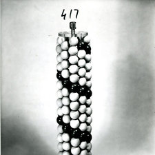 photo of model shaped like a cylinder of regularly stacked white spheres except for a row of coloured spheres twisting up the column