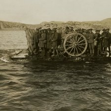 image of a raft pulled by tow ropes crowded with men in heavy coats with the large wheel of a field gun near the centre of the raft