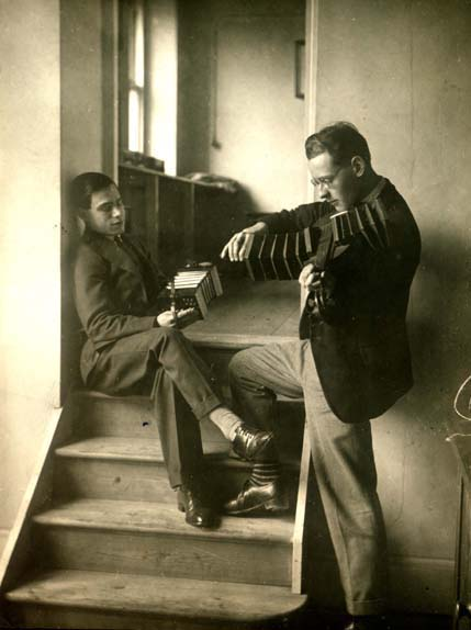 Students demonstrating a concertina and a wind fiddle or bellows fiddle, both invented by Wheatstone (Ref: K/PH7/1/7)